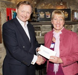 Head of Communications Claire receives cheque from the sponsored cycle ride