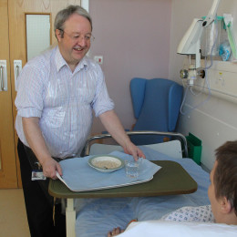 Colleague Ian, who has been volunteering as a mealtime companion, serving a meal to a patient