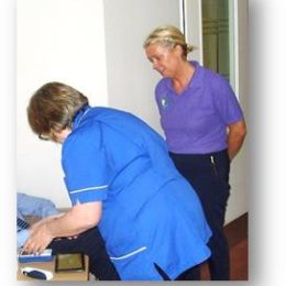 Community Nurse treats patient while care home staff member looks on