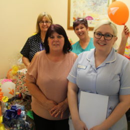 Staff surrounded by all the generous easter raffle prizes they have up for grabs