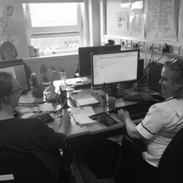 Picture of ISPA team sat around the same desk at the University Hospital of Hartlepool