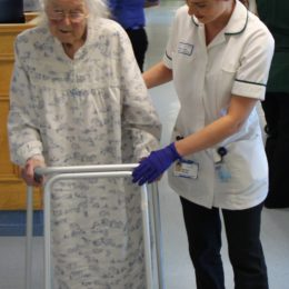 Staff member helps elderly patient along corridor