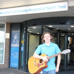 Jason Wilson, our singing volunteer poses with his Guitar at North Tees Hospital main entrance.