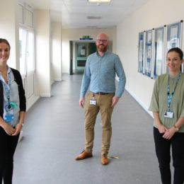 Children speech and language team standing in hospital corridor.