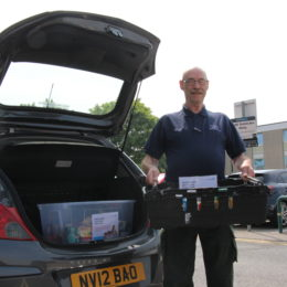Volunteer driver stands at the boot of his car with some of the Trusts ongoing foodbank donations