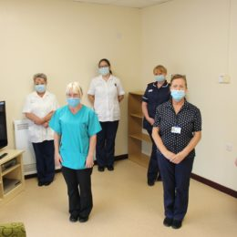 Joint replacement team stand spaced apart in units waiting room
