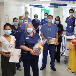 Respiratory team stand in departments corridor celebrating their team of the month win with hamper and other goodies