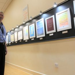 Chaplain Robert Cooper stands in front of some of the calligraphy artwork current on display in the Trusts spirituality centre