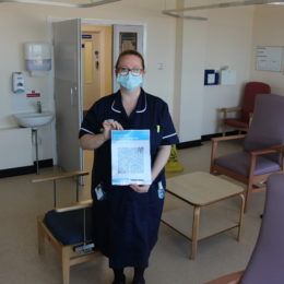 Staff member holds up new QR barcode poster in the waiting room of the surgical decision unit