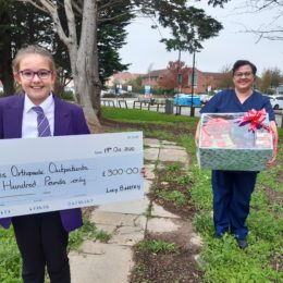 Lucy Bettley and Mihaela McDonald hold cheque donation and basket of goodies outside of North Tees Hospital