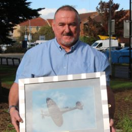Philip Elder proudly holds up his NHS Spitfire photograph donation