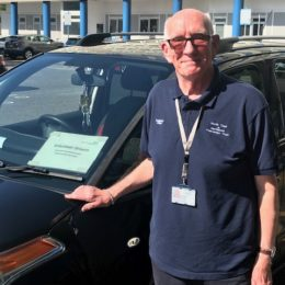 Volunteer Driver Tommy Young stood in front of his black car