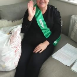 Amanda McNeany sat on her sofa at home, waves at the camera