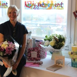 Carol Bowler smiles while holding flowers, stood in-front of her cake and gifts as she celebrates her retirement