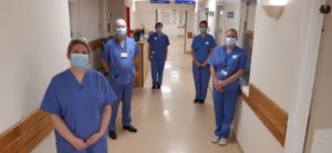 Reasearch vaccine trial team stand spaced out in hospital corridor