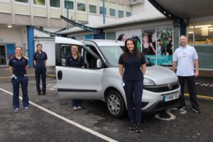 • Bev Marwood – senior physiotherapist and trainee ACP • Hannah Scott, specialised therapy assistant & student physio • Jessica Tindall – Band 5 physiotherapist • Shannon O'Dwyer-Lunn, specialised therapy assistant • Mark Ryder – frailty coordinator - posing with a Trust car