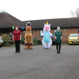 Care home team standing outside their care home in Thornaby with staff in Unicorn and Dinosaur costumes
