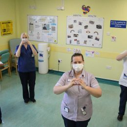 The team in centralised outpatients standing in the waiting area by their information board.