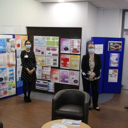 Quality improvement leads stood by display posters of innovation projects
